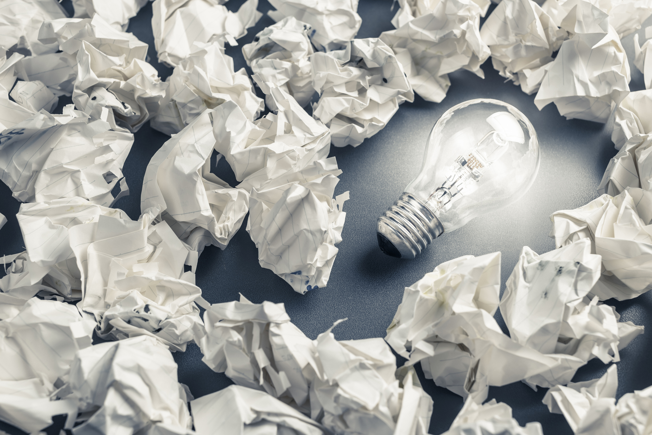 Glowing light bulb among the crumpled rubbish paper
