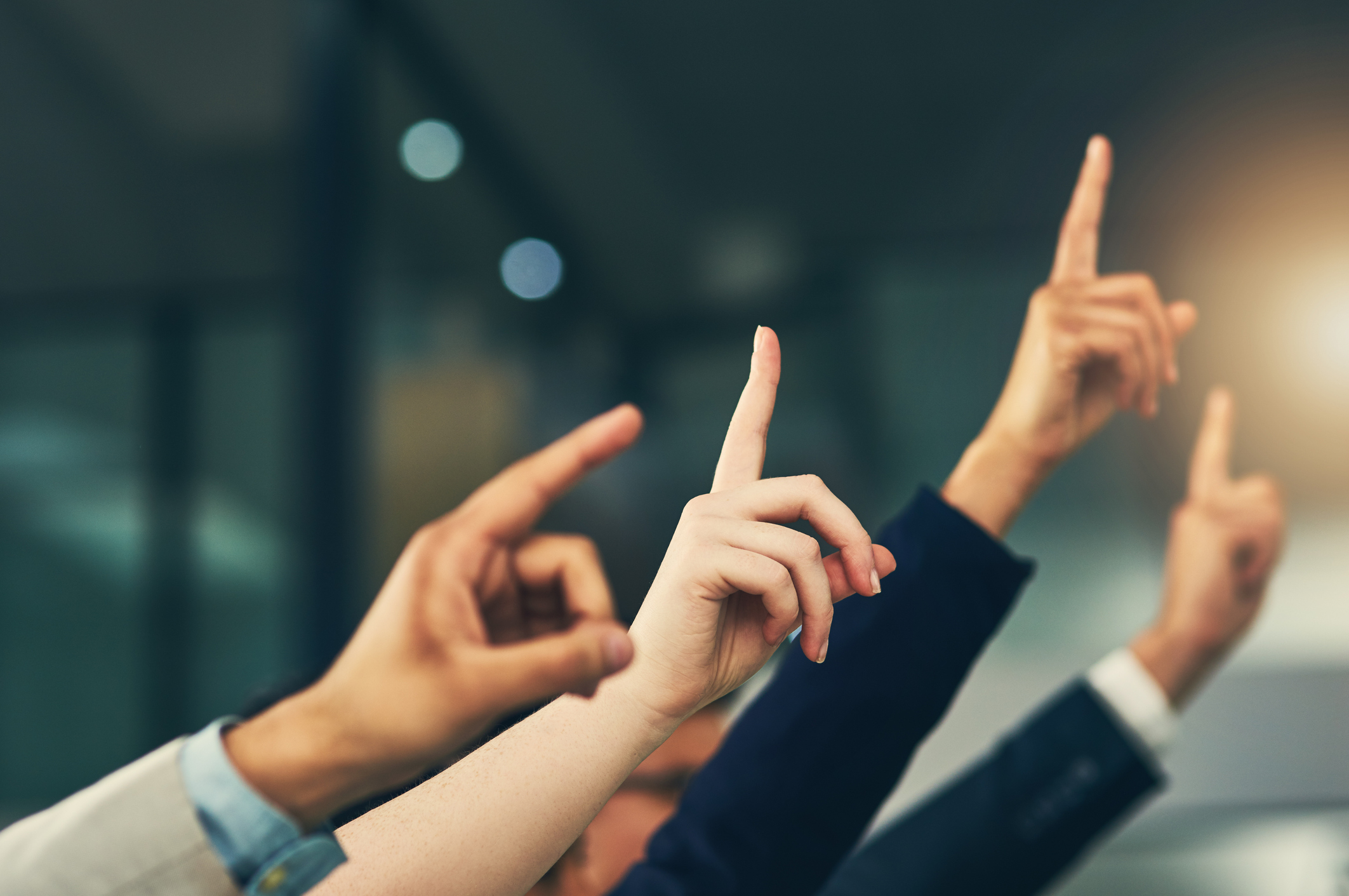 Cropped shot of a group of businesspeople raising their hands