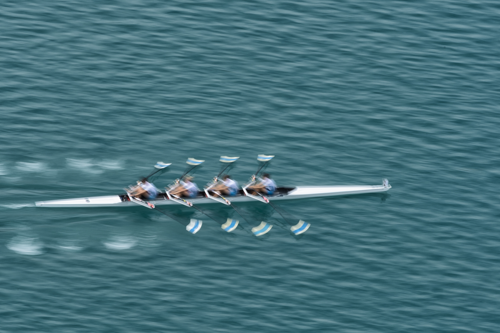 Upper view of quadruple scull rowing team on the water, blurred motion